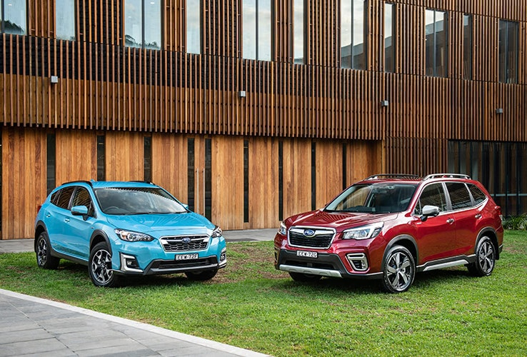 Blue and red Subaru Hybrids parked outside building