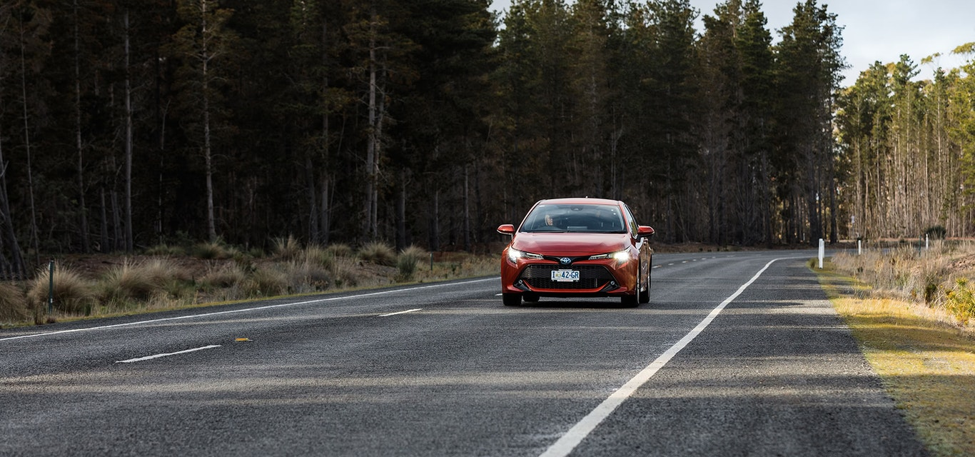 Red Toyota hatchback driving along tree-lined road