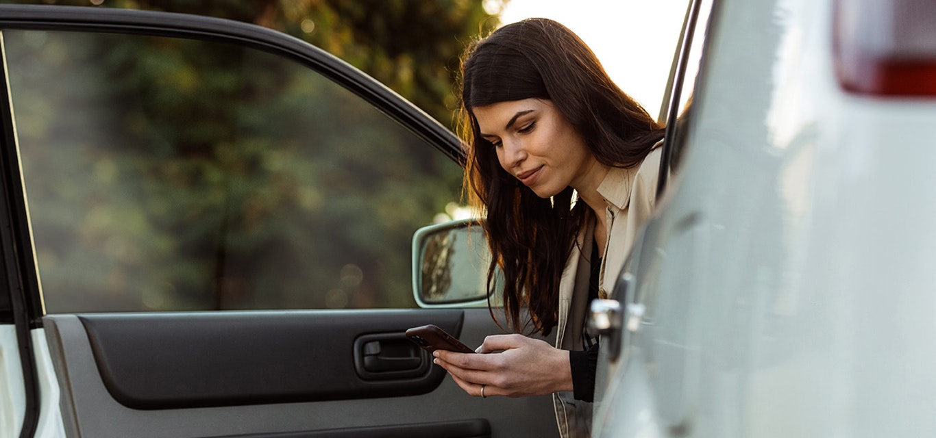 Woman sitting in car with door open looking at mobile phone