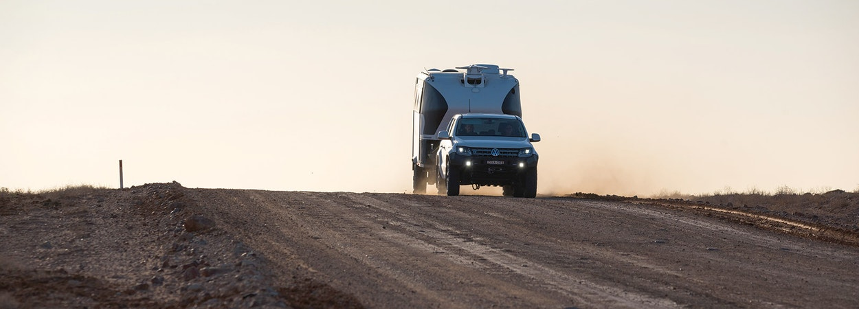 VW pulling a caravan across a remote road