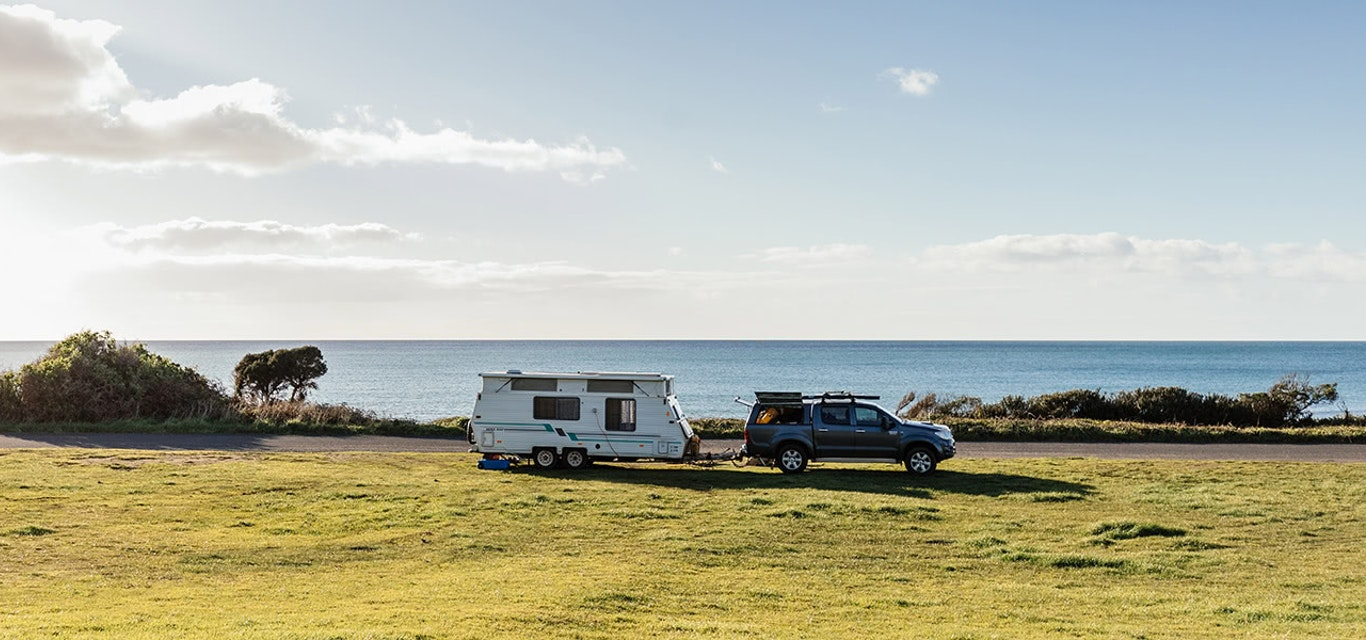 Caravan attached to a ute in a grassy paddock next to a waterway