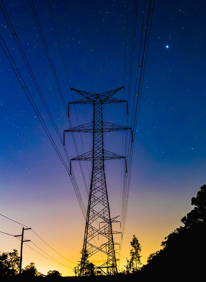 Night-time photo of an electricity tower on a yellow to blue sunset sky