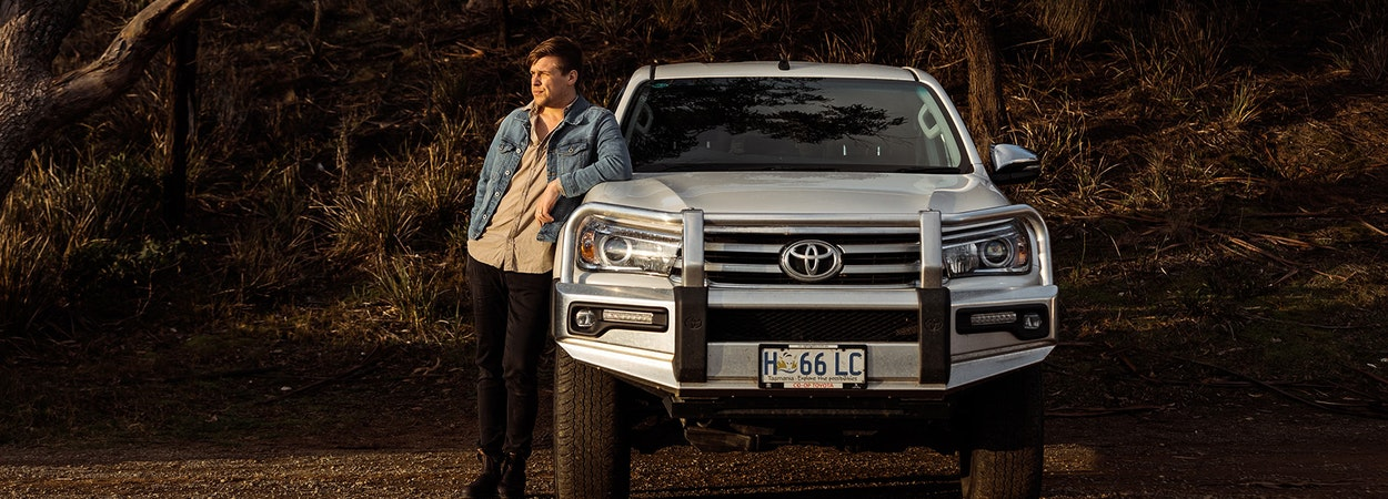 Young driver leaning on a Toyota Ute bonnet in the bush