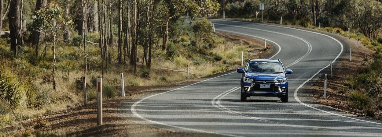 Blue Mitsubishi driving along rural road