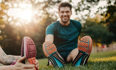 Two people stretching before physical activity
