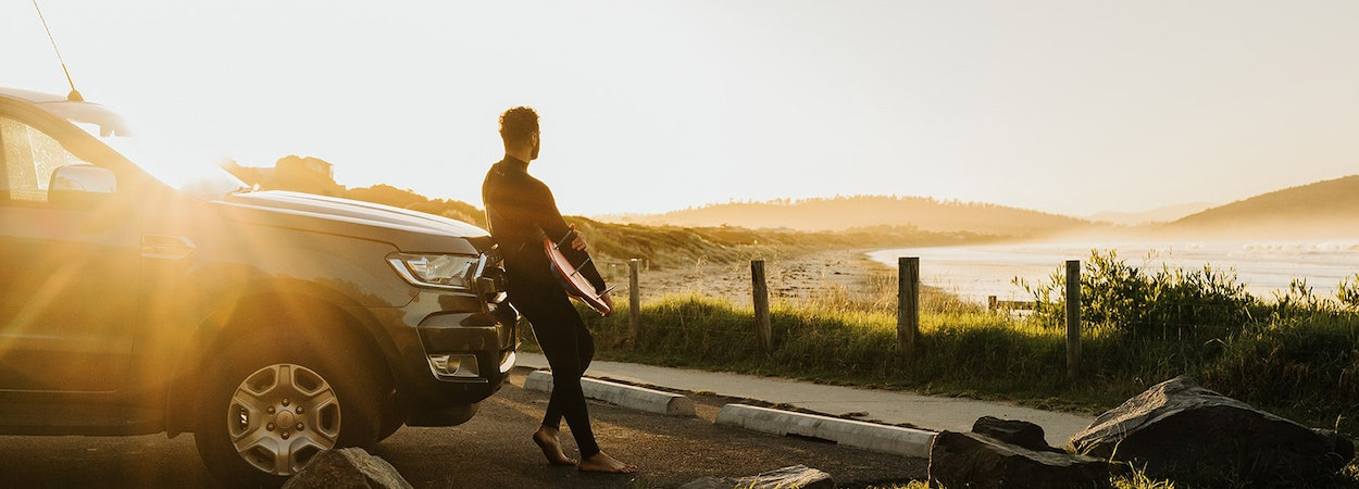 Surfer admiring the view over the beach leaning on his car