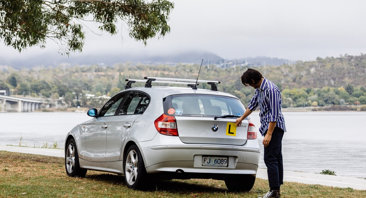 Man affixing learner plate to car