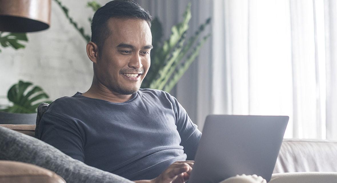 Man smiling while using laptop