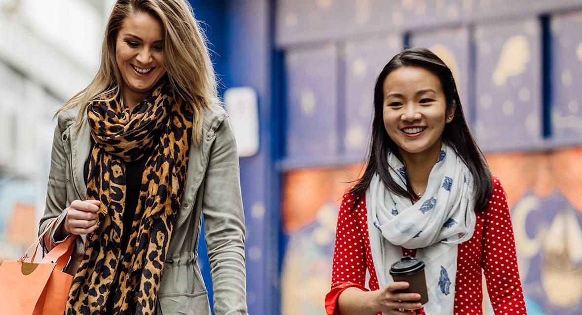 Two women holding shopping bags walking down a street