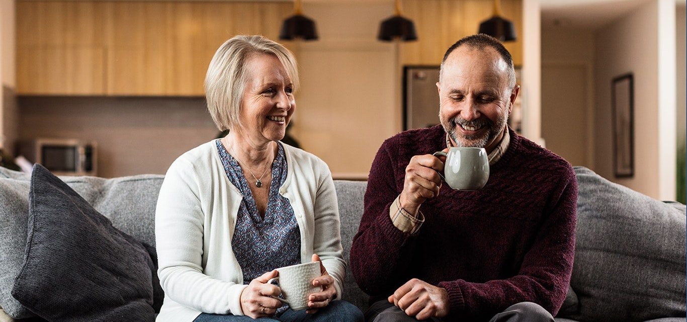 Man and woman enjoying a hot drink on the couch