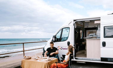 Young couple enjoying a beachside breakfast next to their motorhome