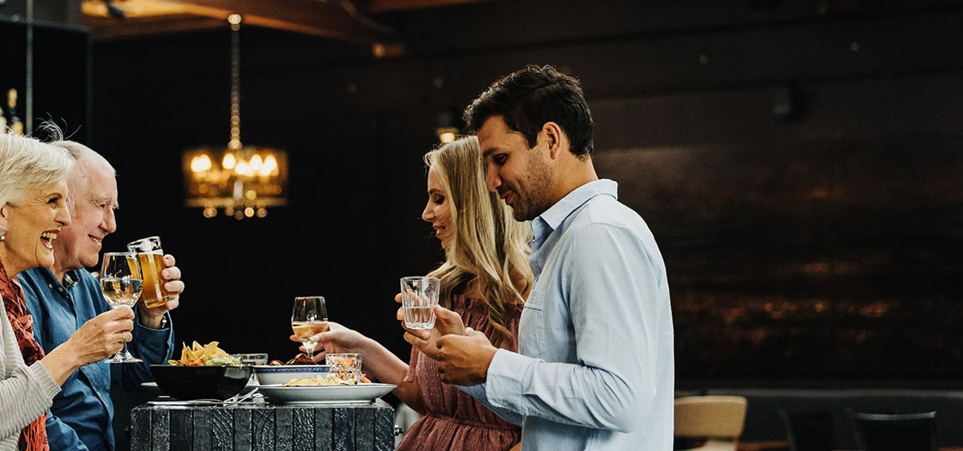 A young and elderly couple toast at a restaurant