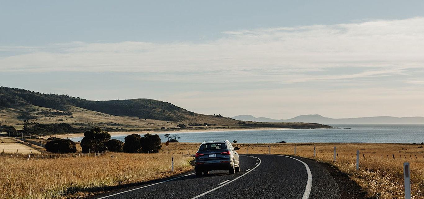 Car driving through a seaside road.