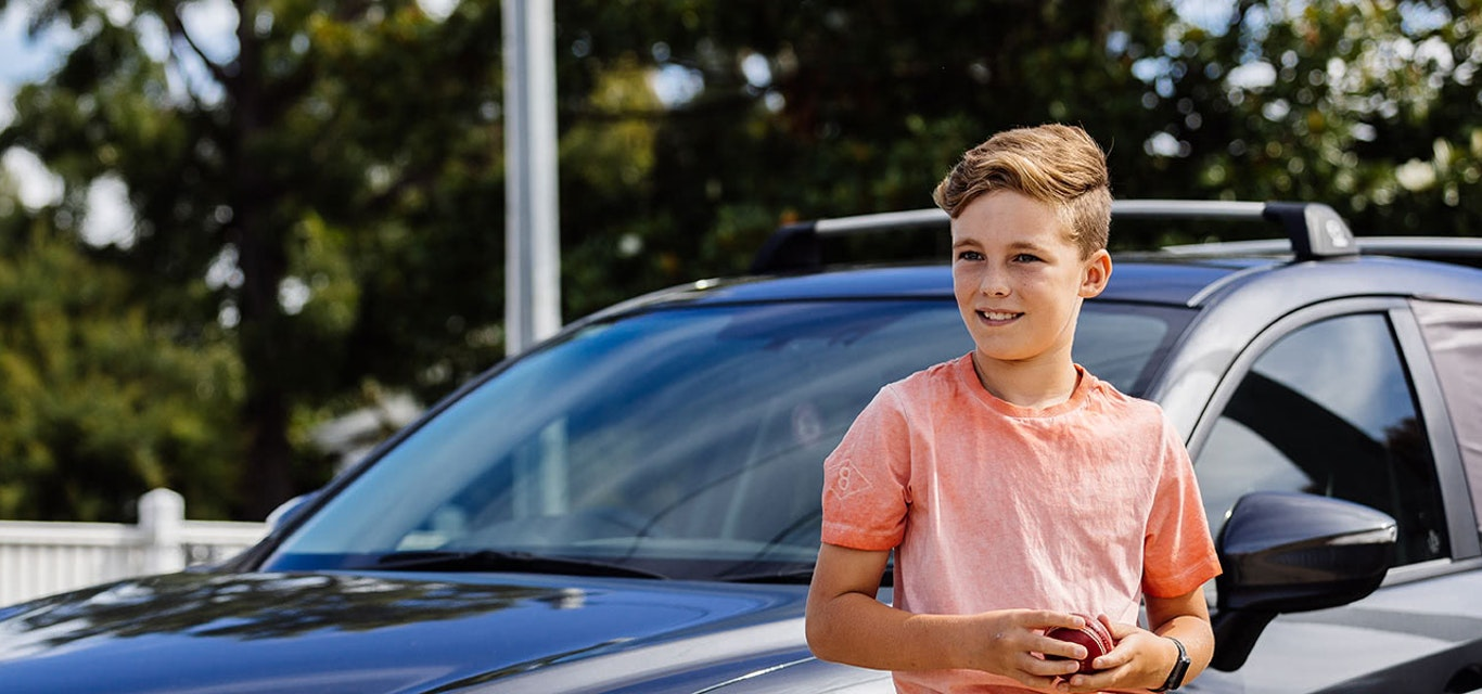 Child standing beside nice car