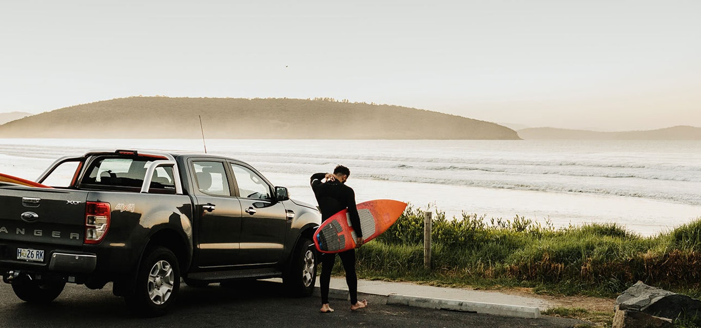 Surfer at beach in car park next to his ute
