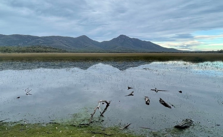 A view of a mountain range from the mouth of a lake.