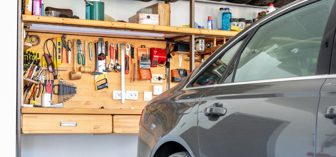 Car in garage with tools on wall