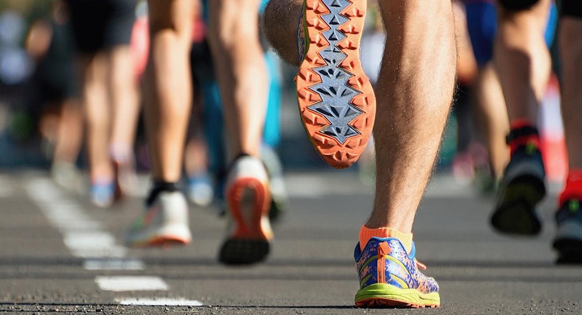 Close-up of marathon runners' feet running along road