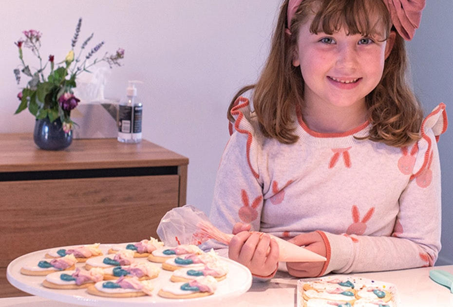 Smiling girl decorating biscuits