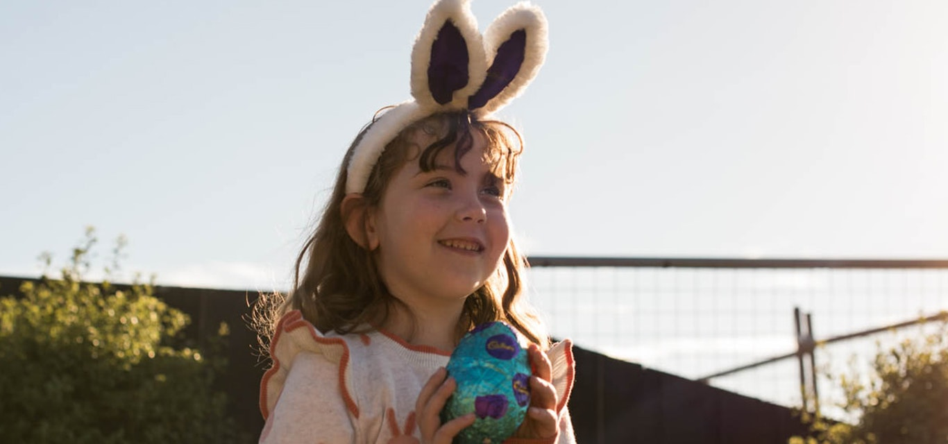 Smiling girl holding Easter egg and wearing rabbit ears