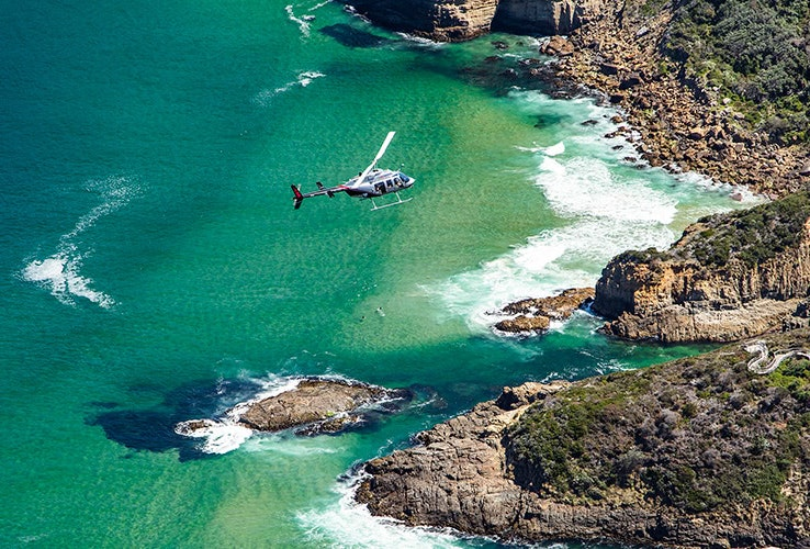 Helicopter flying over a picturesque rocky bay