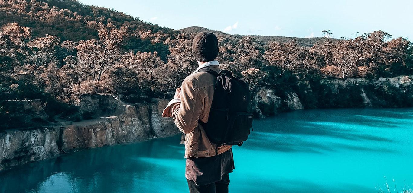 Hiker overlooking pristine blue waters of Little Blue Lake near Derby