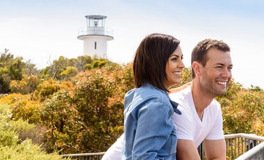 Young couple at a lookout with a lighthouse in the background
