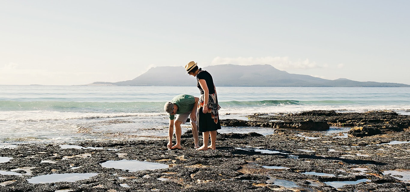 A young couple investigating rock pools on a beach