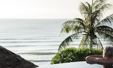 Older gentleman relaxing in pool overlooking exotic location.