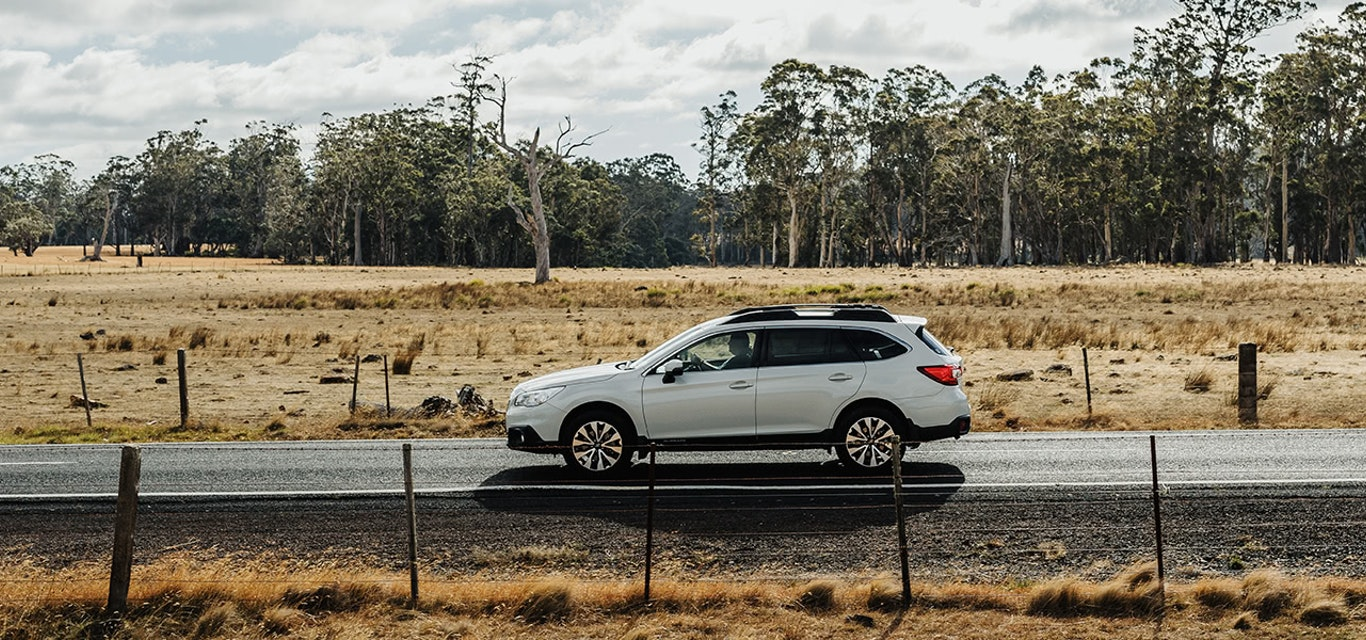 Subaru Outback driving along country road