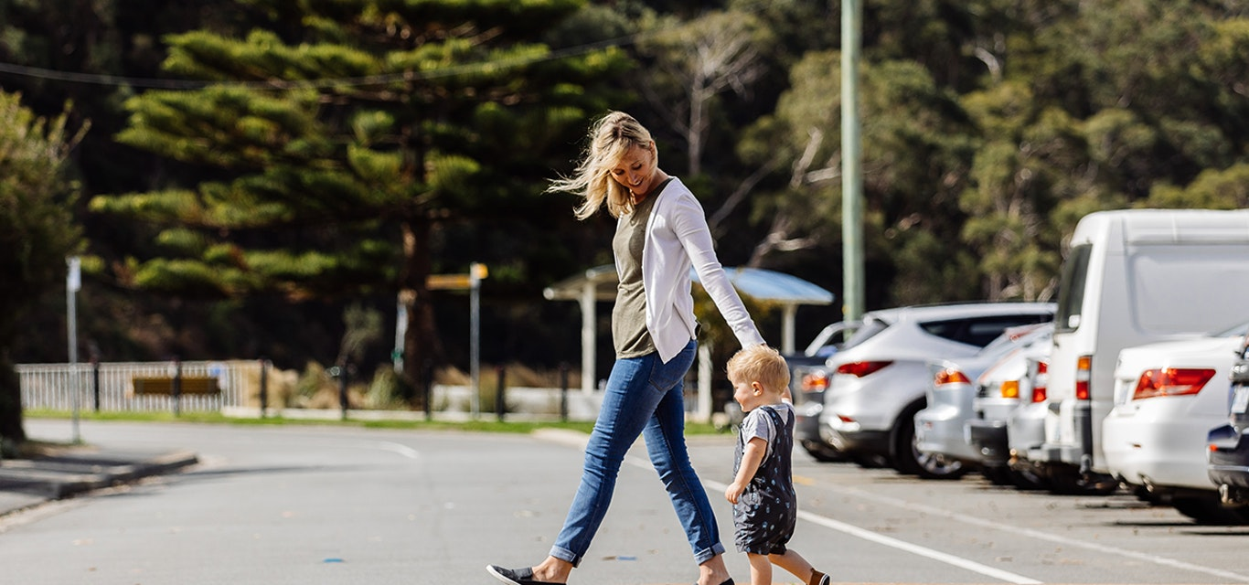 Woman and child crossing the road holding hands