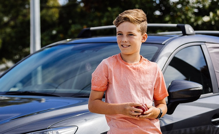 Boy holding cricket ball leaning on car