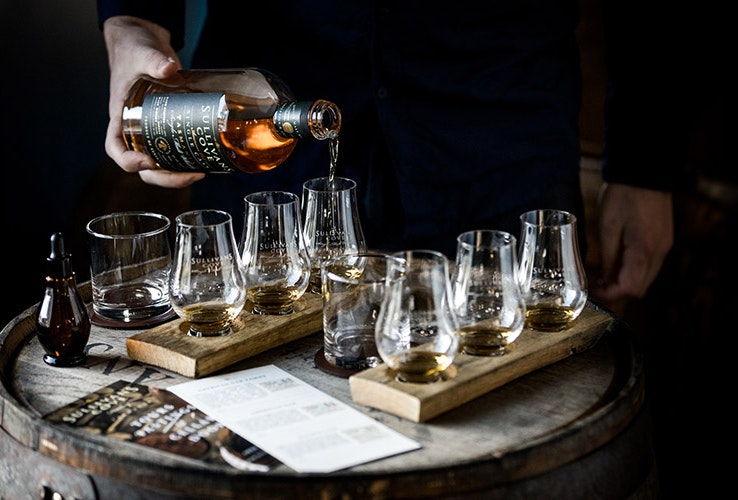 Pouring whiskey into glasses.