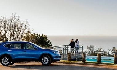 People looking out over the ocean from a lookout point