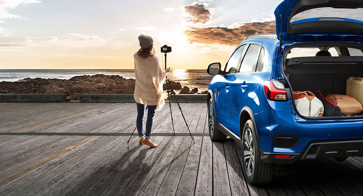 Woman taking a photo of the seascape with tripod set up next to her car