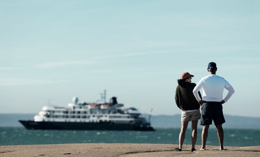 Two people looking at a cruise ship