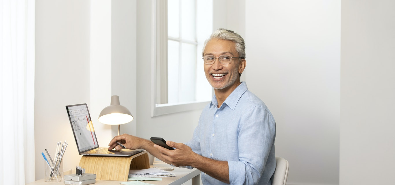 Man sitting at desk wearing glasses and smiling