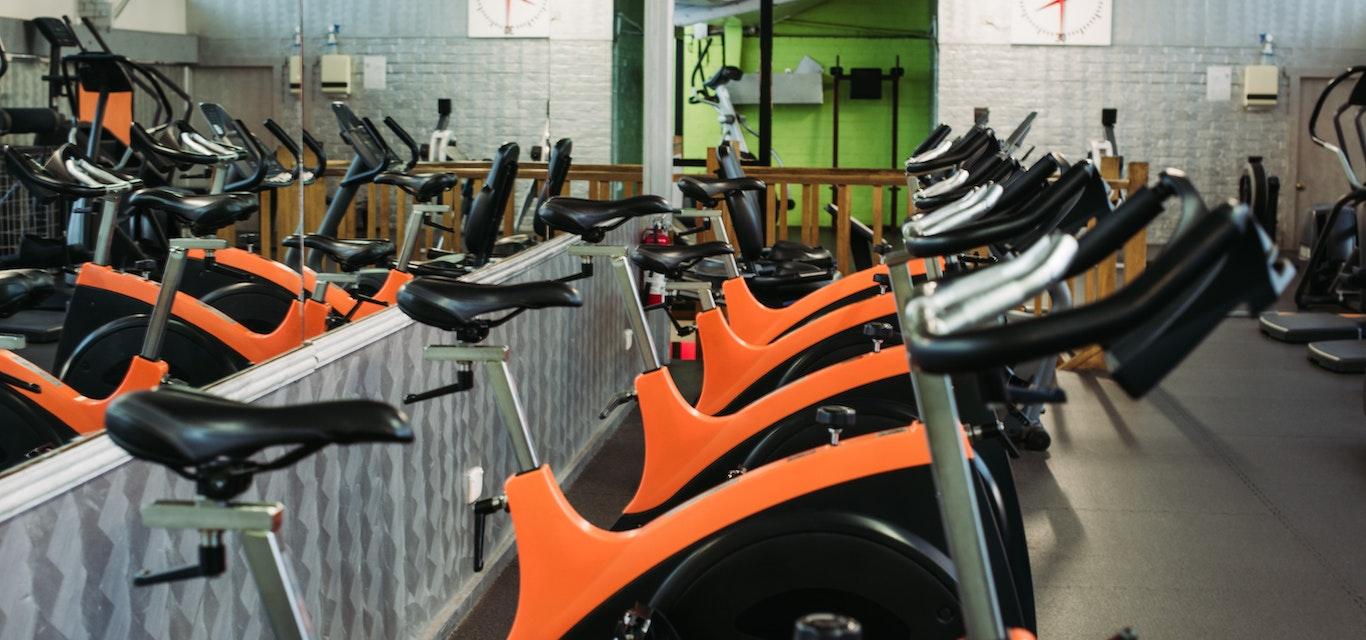 Orange exercise bikes in gym