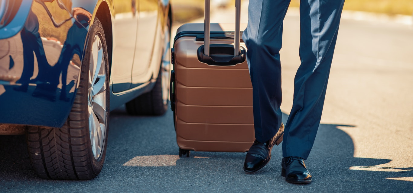 Person wheeling suitcase next to car