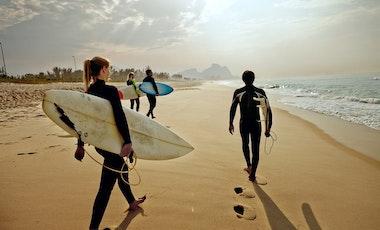 People walking along beach holding surfboards
