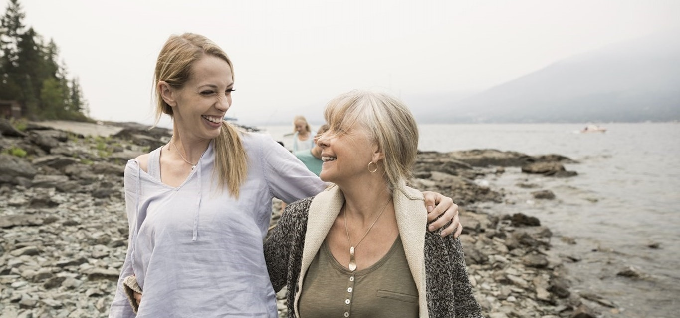 Two women walking on beach smiling at each other