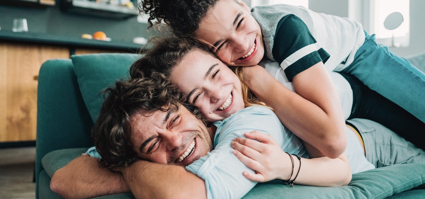 Father and children smiling on couch