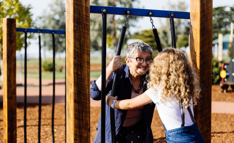 Gran and child playing peek a boo at the park