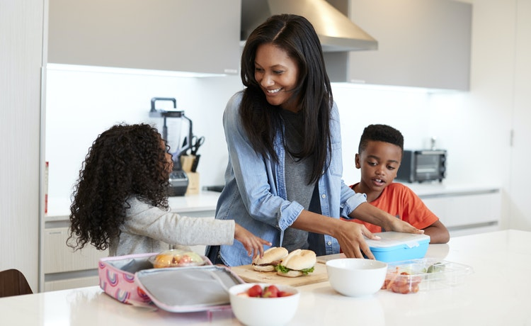 Woman packing lunchboxes with her two children