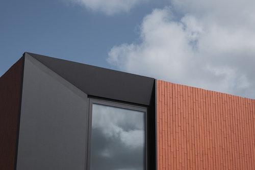 Skilpod modern design houtskeletbouw woning, detail afgeschuind zwart raam en rode steen