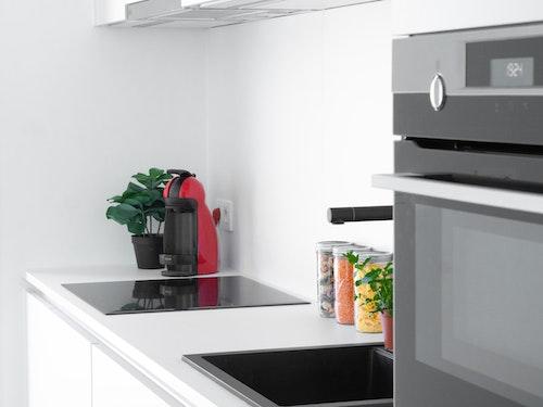 Detail van een Skilpod keuken, zwarte gootsteen en toestellen van AEG: inductiekookplaat, combi-oven, dampkap
