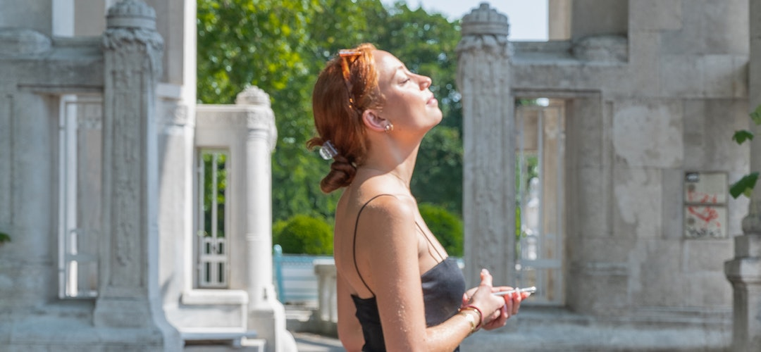 A white woman with red hair turns her face to the sun, eyes closed. Her hands are holding a cellphone in front of her, and there are stone columns in the background.