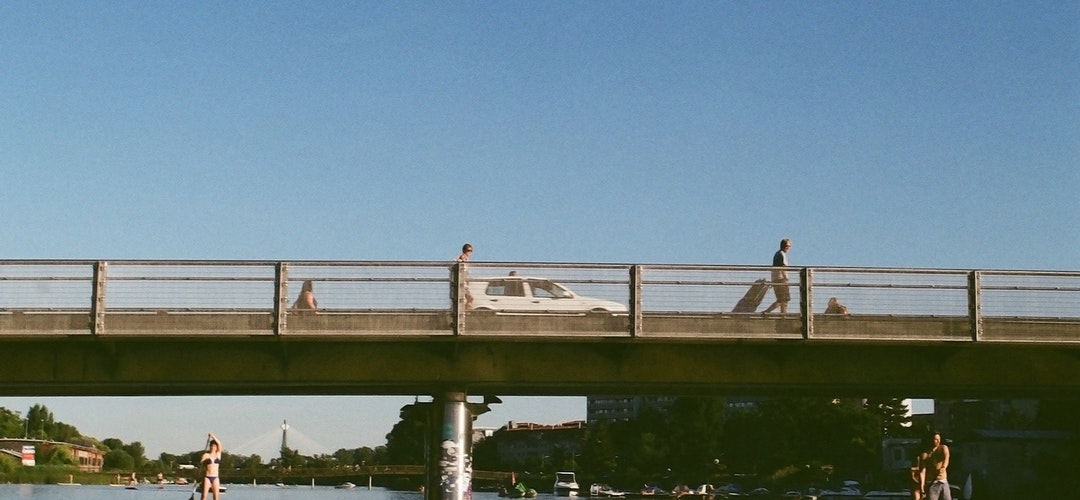 A low metal bridge covers a wide waterway. Two people in swimwear hold paddles as they use stand-up paddleboards beneath the bridge.