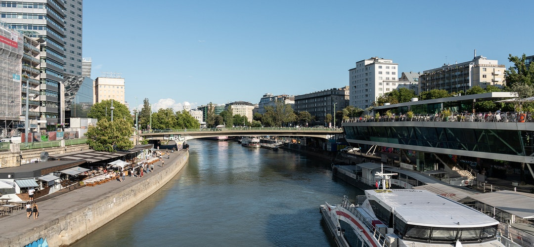 A narrow waterway winds its way through an urban environment, with a large boat docked on the side. It's sunny and bright, with trees in the background.