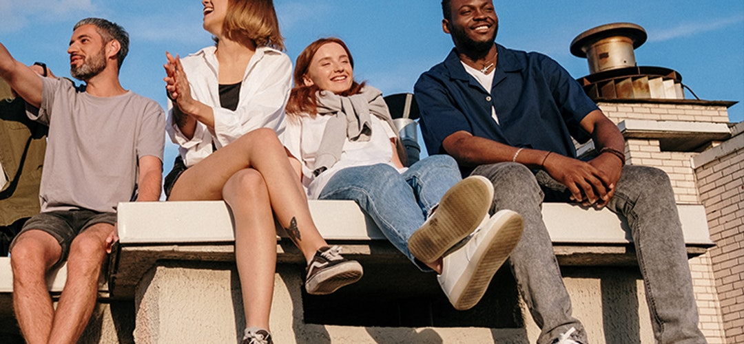 Four young people sit on a raised stone surface, smiling and pointing. They're squinting into the day's fading light.